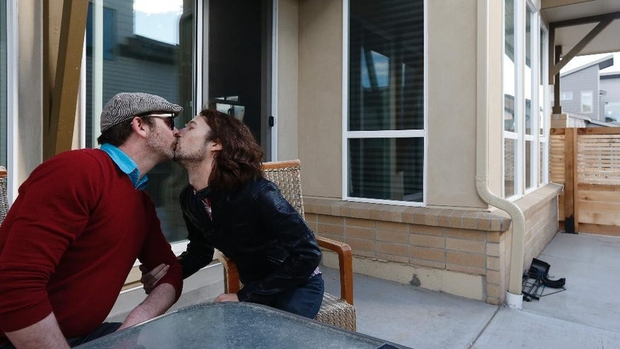 File - In this March 13, 2014 file photo, Dave Mullins, right, kisses his husband Charlie Craig, on the patio of their home in Westminster, Colo. The suburban Denver baker who refused to make a wedding cake for Mullins and Craig is to argue Tuesday, July 7, 2015 before the Colorado Court of Appeals that his religious beliefs should protect him from sanctions against his business. (AP Photo/Brennan Linsley, file)