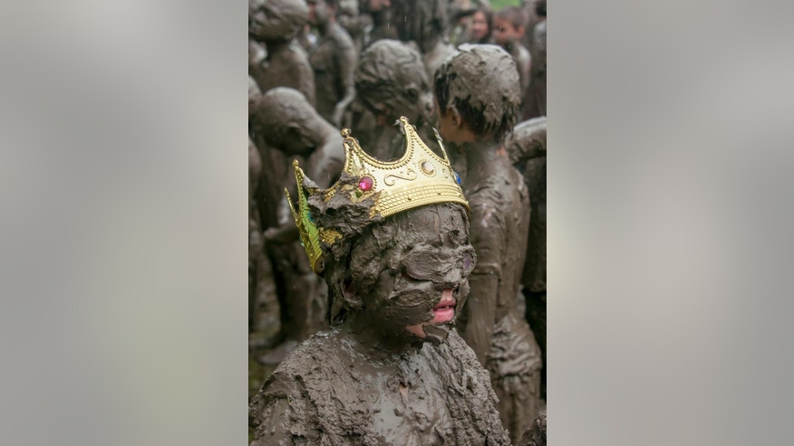 Six-year-old Emileigh Powers, of Troy, New York, was named Mud Queen at the annual Mud Day in Nankin Mills Park in Westland, Mich. on Tuesday, July 7, 2015. (David Guralnick/The Detroit News via AP) DETROIT FREE PRESS OUT - HUFFINGTON POST OUT - NO MAGS - NO SALES- NO ARCHIVE - MANDATORY CREDIT