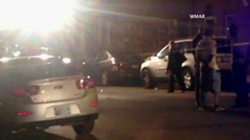In this image taken from video, police investigate the scene of a shooting, Tuesday, July 7, 2015, in Baltimore. Baltimore police say four people have been shot, three fatally, near the University of Maryland, Baltimore, campus. (WMAR via AP)