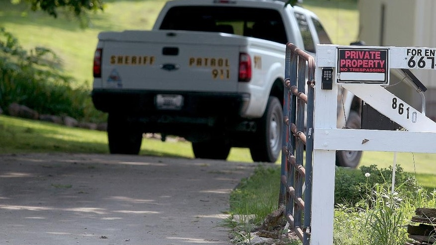 This Saturday, July 4, 2015 photo shows a Buchanan County, Missouri, Sheriff's vehicle outside the St. Joseph home where James and Beverly Johnson were found dead. Authorities say their 16-year-old grandson has been charged in their slayings. It was the first of two fatal tragedies to strike the family in just four days, a relative told The Associated Press. On Tuesday James brother, Michael Johnson, and his son were killed in a collision between a small plane and an F-16 fighter jet in South Carolina. (Jessica Stewart/St. Joseph News-Press via AP)