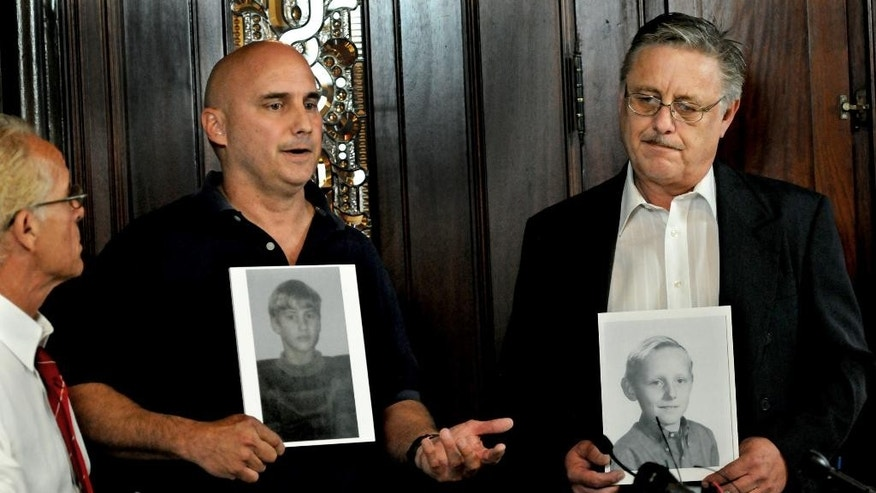 David Lundquist, center, and Steven Josephson, right, holding photos of themselves as boys, announce that they are their lawsuits against Boy Scouts of America, Thursday, July 9, 2015, in St. Paul, Minn. The two are claiming that they were sexually abused as scouts by troop leaders in St. Paul. (Jean Pieri/The St. Paul Pioneer Press via AP)  MINNEAPOLIS STAR TRIBUNE OUT; MANDATORY CREDIT