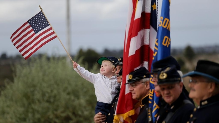 Stephen Tisch, 2, poses for a picture with Civil War re-enactors before Army Sgt. Charles Schroeter, who was awarded the Congressional Medal of Honor for gallantry in an 1869 battle during the Indian Wars is re-interred with full military honors at Miramar National Cemetery Thursday, July 9, 2015 in San Diego. Schroeter's remains were located only recently, when the Congressional Medal of Honor Historical Society traced them to San Diego's Greenwood Memorial Park, where they had rested since 1921. The remains were interred in an unmarked crypt, along with other unclaimed remains. (AP Photo/Chris Carlson)