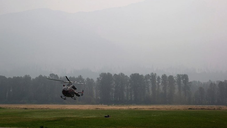 Smoke from wildfires fills the air as a helicopter carrying British Columbia Premier Christy Clark arrives at Pemberton Fire Base in Pemberton, British Columbia, Wednesday, July 8, 2015. Firefighters made some progress Wednesday in quelling hundreds of wildfires raging across central and western Canada that are threatening thousands of people and triggering air quality warnings across the country and in the U.S. West and Midwest, authorities said. (Darryl Dyck/The Canadian Press via AP) MANDATORY CREDIT