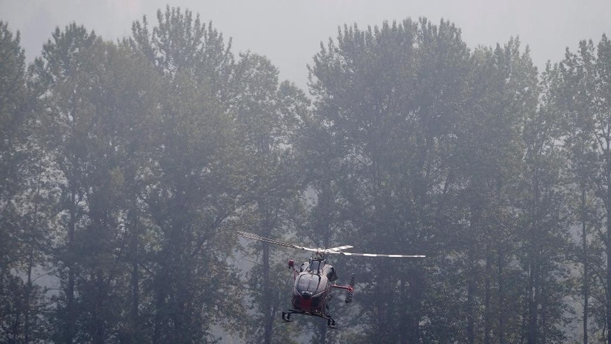 Smoke from wildfires fills the air as a helicopter carrying British Columbia Premier Christy Clark arrives at the Pemberton Fire Base in Pemberton, British Columbia, Wednesday, July 8, 2015. Firefighters made some progress Wednesday in quelling hundreds of wildfires raging across central and western Canada that are threatening thousands of people and triggering air quality warnings across the country and in the U.S. West and Midwest, authorities said. (Darryl Dyck/The Canadian Press via AP) MANDATORY CREDIT