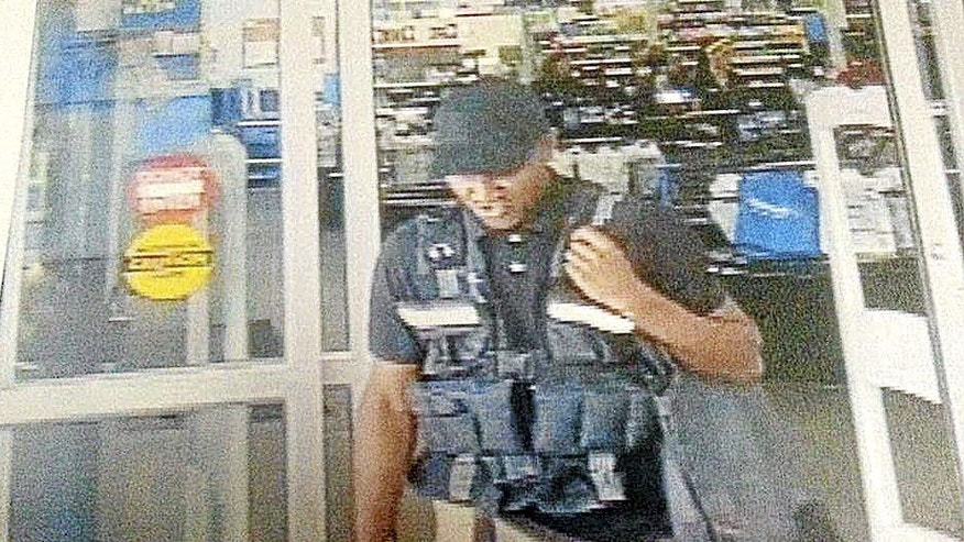 FILE - In this July 4, 2015, file frame from surveillance video provided by the Bristow Police Department, a man leaves with more than $75,000 from a Wal-Mart after disguising himself as an armored truck driver in Bristow, Okla. A Wal-Mart manager and his daughter were arrested Wednesday, July 8 in connection with an investigation. (Bristow Police Department via AP, File)