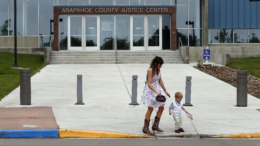 A woman and her son exit the Arapahoe County District Court, where the trial of Aurora movie theater shooter, James Holmes, continues, Wednesday, July 8, 2015, in Centennial, Colo. Prosecutors are tearing into the testimony of a second defense expert who concluded the shooter was so mentally ill that he couldn't tell right from wrong when killed 12 people and injured 70 during a packed midnight movie premiere three years ago. (AP Photo/Brennan Linsley)