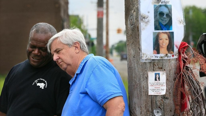 In this photo taken June 15, 2015, Dave Lawrence, right, and Steven Goodin share a moment after a prayer at the site where Lawrence's 16-year-old granddaughter Paige Stalker was killed in Detroit. A few days after Paige's slaying in December, Christina Samuel was shot and killed not far away. Chris Samuel, Christina's father, and Lawrence have launched a foundation with others aimed at establishing neighborhood groups and developing safety education programs. (AP Photo/Carlos Osorio)