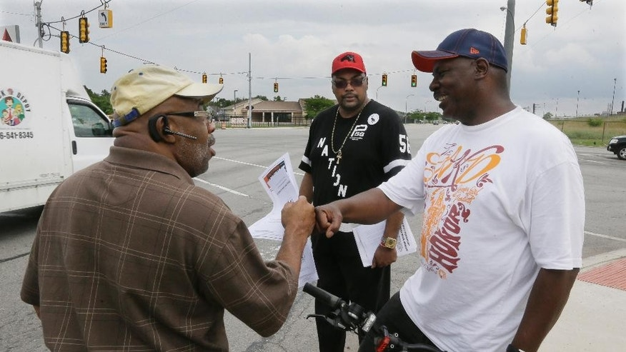 In this photo taken June 15, 2015, Chris Samuel, left, gets a fist bump from supporter Milton Stanciel after talking about rising crime in Detroit. Samuel's 22-year-old daughter, Christina Samuel, was gunned down in December a car on Detroit's eastside. Samuel and Dave Lawrence, whose 16-year-old daughter, Paige Stalker was shot and killed days earlier, have helped launched a foundation aimed at establishing neighborhood groups and developing student safety education programs. (AP Photo/Carlos Osorio)