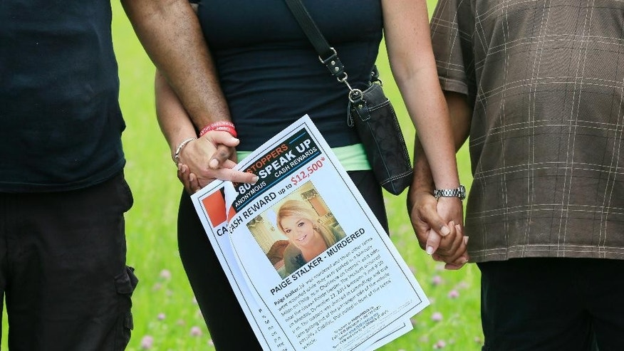 In this photo taken, June 15, 2015, a supporter holds a Crime Stoppers poster seeking information on the murder of Paige Stalker ,during a prayer at the site where the 16-year-old was shot and killed in Detroit. Paige's grandfather, Dave Lawrence, and Chris Samuel, whose 22-year-old daughter, Christina Samuel, was killed nearby just days later, have launched a foundation with others aimed at establishing neighborhood groups and developing safety education programs. (AP Photo/Carlos Osorio)