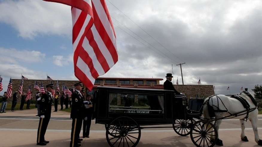 July 9, 2015: An honor guard places the remains of Army Sgt. Charles Schroeter, who was awarded the Congressional Medal of Honor for gallantry in an 1869 battle during the Indian Wars in the back of a a horse-drawn hearse at Miramar National Cemetery in San Diego.