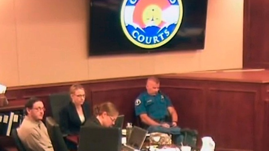 In this image taken from Colorado Judicial Department video, Colorado theater shooter James Holmes, upper left in blue shirt, joins others in standing as the jury, not pictured, is brought into the courtroom, during Holmes' trial in Centennial, Colo., Friday, July 10, 2015. The defense in the Colorado theater shooting trial rested its case Friday after trying to show James Holmes was legally insane when he carried out the deadly 2012 attack, suffering from delusions that each person he killed would increase his self-worth. (Colorado Judicial Department via AP, Pool)