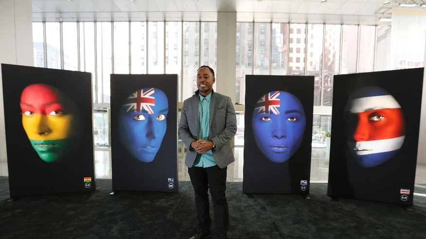 Artist Robert Young poses with his artwork Friday, July 10, 2015, in Toronto. Robert Young was able to find young women living in Toronto with roots to each of the 41 nations represented in the Pan American games. He painted their faces in the colors of the national flags, a work that's turned into a large exhibition in downtown Toronto.  (AP Photo/Julio Cortez)