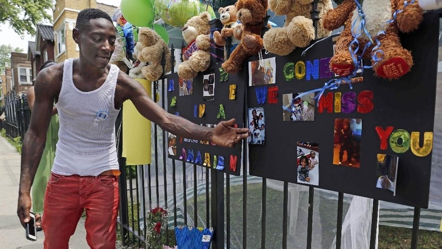 FILE - In this July 6, 2015, file photo, Antonio Brown, father of Amari Brown, speaks near a sign honoring his son, in Chicago. Seven-year-old Amari was among three people who were shot and killed overnight during a weekend outbreak of gun-related violence in Chicago. Homicides and shooting incidents in Chicago are up roughly 20 percent from the same period last year. (AP Photo/Christian K. Lee, File)