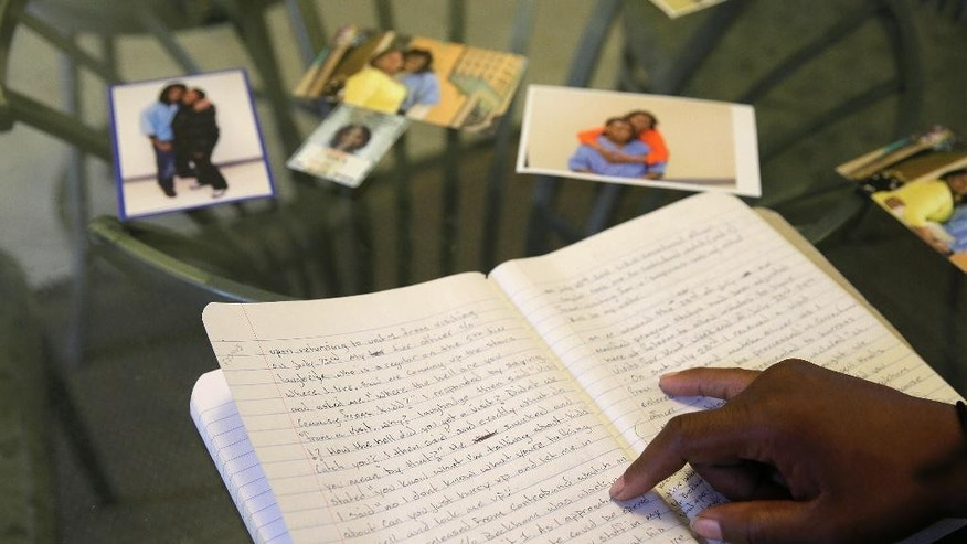 """In this Tuesday, May 5, 2015 photo, Raymond Kidd, a former state prison inmate who was placed on contraband watch, looks over a journal he kept while in prison, at his home in San Francisco. California's controversial method of recovering contraband from inmates uses """"potty watches"""" where inmates are handcuffed and shackled for days or even weeks while guards watch around-the-clock until nature takes its course. State reports show that they produced results less than 41 percent of the time. (AP Photo/Eric Risberg)"""