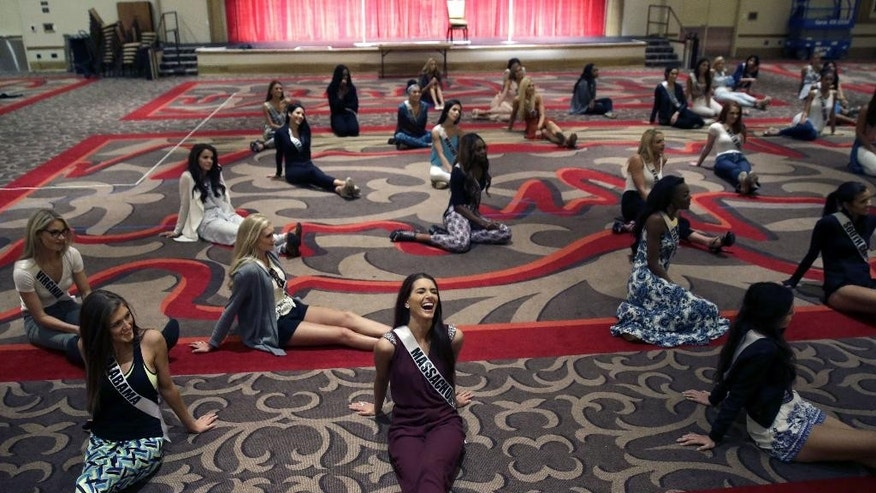 In this Monday, July 6, 2015 photo, Miss Massachusetts Polikseni Manxhari laughs during rehearsal for the upcoming Miss USA Pageant in Baton Rouge, La. Pageant co-owner Donald Trump recently made comments painting Mexican immigrants as criminals. (AP Photo/Gerald Herbert)