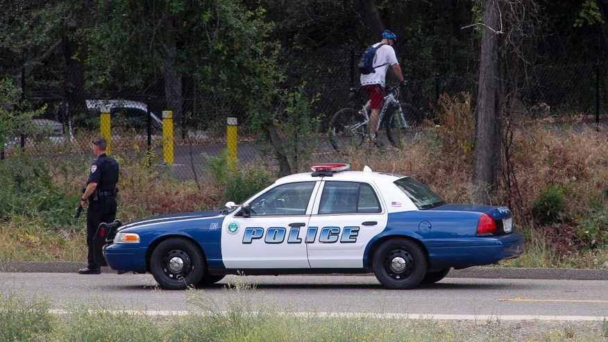 A Redding police officer aids in the search for Matthew Graham at the entrance to the parking lot near the Diestelhorst Bridge and the Sacramento River Trail, Saturday, July 11, 2015, in Redding, Calif. Graham, the subject of a manhunt after he stole a gun and fled, is considered a person of interest in the disappearance of his 6-month-old daughter in Northern California, authorities said.  (Greg Barnette/The Record Searchlight via AP) MANDATORY CREDIT