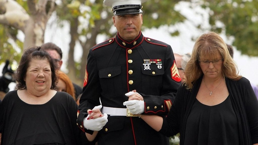 "Retired Marine Sgt. Robert Acosta escorts his mother Dianna Bedwell, left, and sister Debbie Apple, as they arrive at Riverside National Cemetery for a service for Cecil ""Paul"" Knutson on Friday, July 10 2015. Cecil, the Fullerton man who along with his wife Dianna Bedwell, got lost on the way from a San Diego County casino to a relative's home in the Riverside County desert. Cecil passed away in the two-week ordeal and his wife survived. (Stan Lim/The Press-Enterprise via AP)"