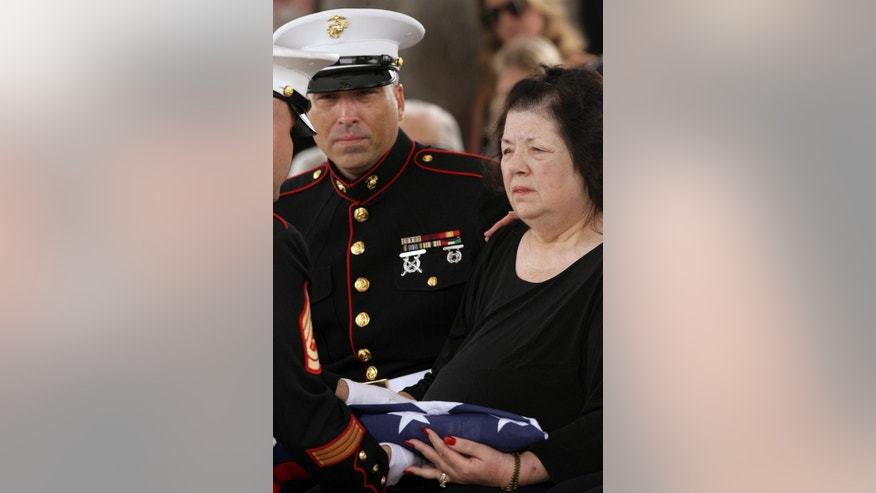"Dianna Bedwell receives a flag will sitting next to her son, retired Marine Sgt. Robert Acosta during a service for her husband, Cecil ""Paul"" Knutson at Riverside National Cemetery on Friday, July 10 2015, in Riverside, Calif. Cecil, the Fullerton man who along with his wife Dianna Bedwell, got lost on the way from a San Diego County casino to a relative's home in the Riverside County desert. Cecil passed away in the two-week ordeal and his wife survived. (Stan Lim/The Press-Enterprise via AP)"