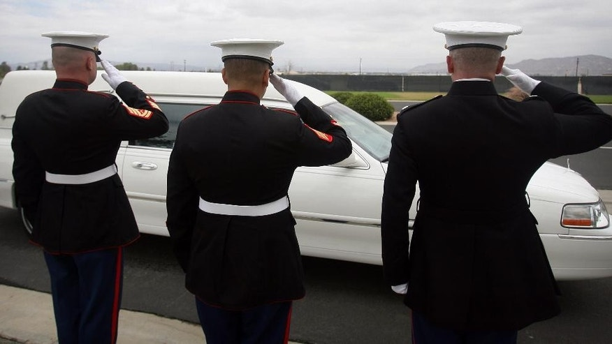 "Marines salute the hearse carrying the ashes of Cecil ""Paul"" Knutson as they arrive at Riverside National Cemetery on Friday, July 10 2015. Cecil, the Fullerton man who along with his wife Dianna Bedwell, got lost on the way from a San Diego County casino to a relative's home in the Riverside County desert. Cecil passed away in the two-week ordeal and his wife survived. (Stan Lim/The Press-Enterprise via AP)"
