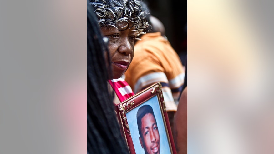 FILE - In this July 7, 2015, file photo, Gwen Carr holds a picture of her son Eric Garner during a news conference in New York with relatives of New Yorkers killed by police. New York City reached a settlement Monday, July 13 with the family of Garner for about $5.9 million, almost a year after the 43-year-old died in police custody. (AP Photo/Bebeto Matthews, File)