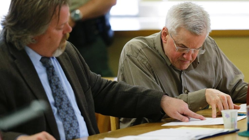 Steven Powell, right, looks at paperwork in a Pierce County Superior courtroom with his attorney, Travis Currie, left, Monday, July 13, 2015, in Tacoma, Wash., shortly after Powell was found guilty of possessing child pornography. Powell is the father of Josh Powell, who killed his two sons and himself in February 2012 while under investigation for the 2009 disappearance of his wife in Utah. (AP Photo/Ted S. Warren)