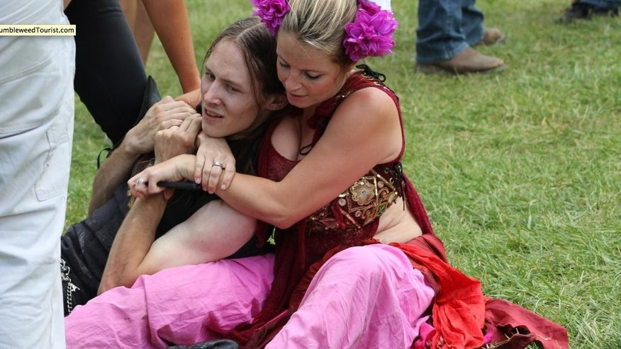 In this Saturday, July 11, 2015 photo, provided by Steven Chapman, a renaissance festival attendee, right, restrains 22-year-old man Connor Ward, after he allegedly made off with a sword at the Colorado Renaissance Festival, in Larkspur, Colo. Ward is facing charges of theft and resisting arrest after authorities say he crashed a jousting performance at the Colorado Renaissance Festival and tried to take a sword. A witness said the man was chased down by two women in costume. (Steven Chapman/TumbleweedTourist.com via AP) MANDATORY CREDIT