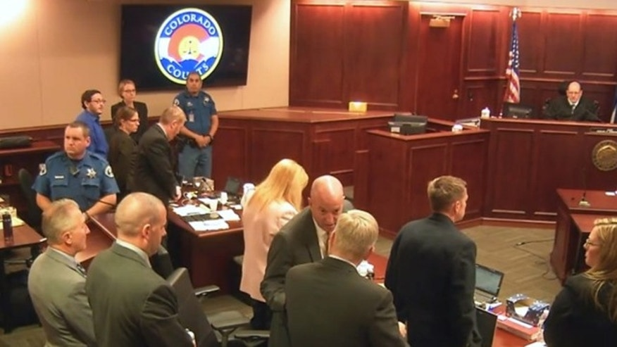 July 10, 2015: In this image taken from Colorado Judicial Department video, Colorado theater shooter James Holmes, upper left in blue shirt, joins others in standing as the jury, not pictured, is brought into the courtroom, during Holmes' trial in Centennial, Colo. (Colorado Judicial Department via AP, Pool)
