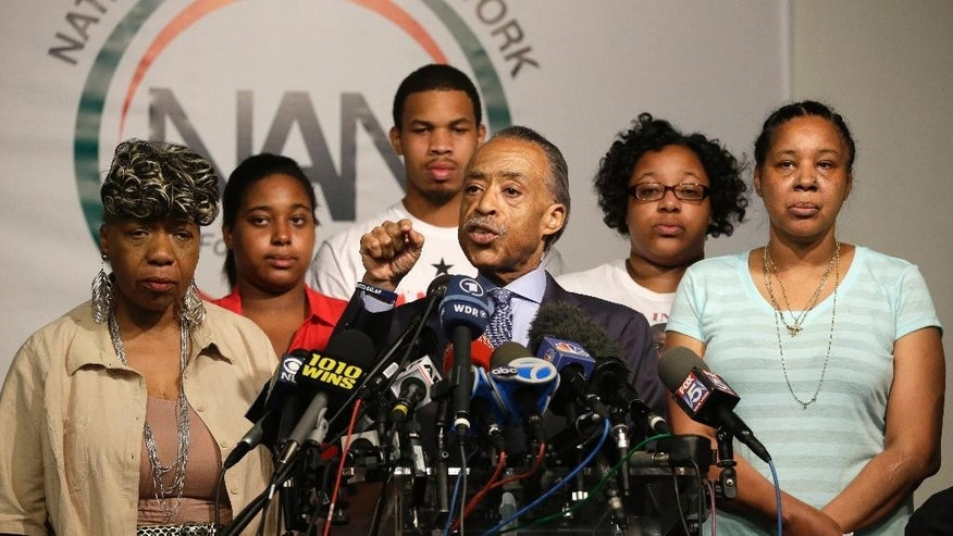 The Rev. Al Sharpton, center, is joined by Eric Garner's mother Gwen Carr, left, daughter Erica Garner, second from left, son Eric Garner, third from left, daughter Emerald Snipes, second from right, and wife Esaw Snipes, as he speaks during a news conference, Tuesday, July 14, 2015, in New York. The family of Garner, a black man who died after being placed in a white police officer's chokehold, discussed the $5.9 million settlement it reached with the city days before the anniversary of his death. (AP Photo/Mary Altaffer)