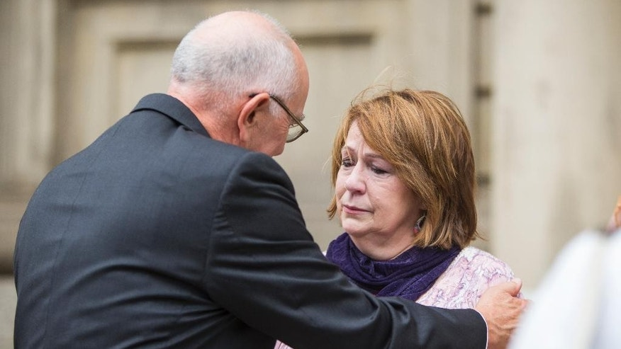 Elaine Sgorcea, the mother of Indianapolis house explosion victim John Dion Longworth, is comforted by Marion County prosecutor Terry Curry following the guilty verdict during the trial on Tuesday, July 14, 2015, outside the St. Joseph County Courthouse in South Bend, Ind. Mark Ray Leonard was found guilty on all 53 counts. (Robert Franklin/South Bend Tribune via AP)