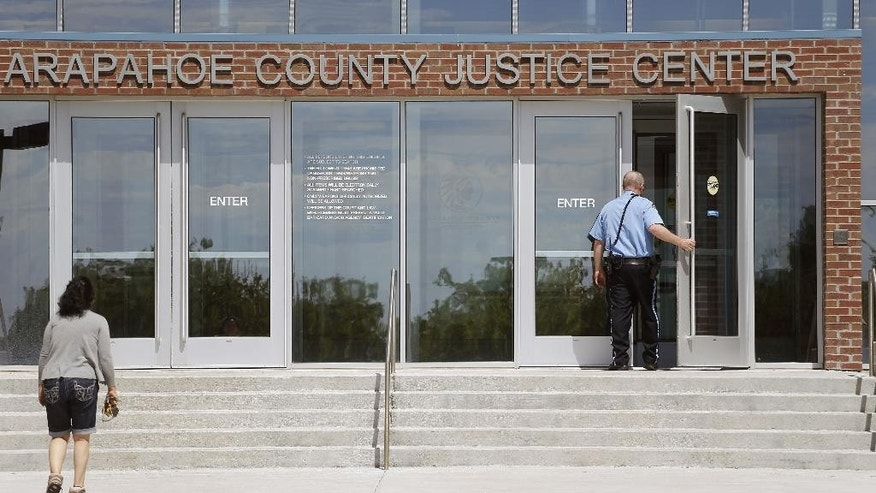 A police officer enters the Arapahoe County District Court on the day of closing arguments in the trial of Aurora movie theater massacre defendant James Holmes, in Centennial, Colo., Tuesday July 14, 2015. (AP Photo/Brennan Linsley)