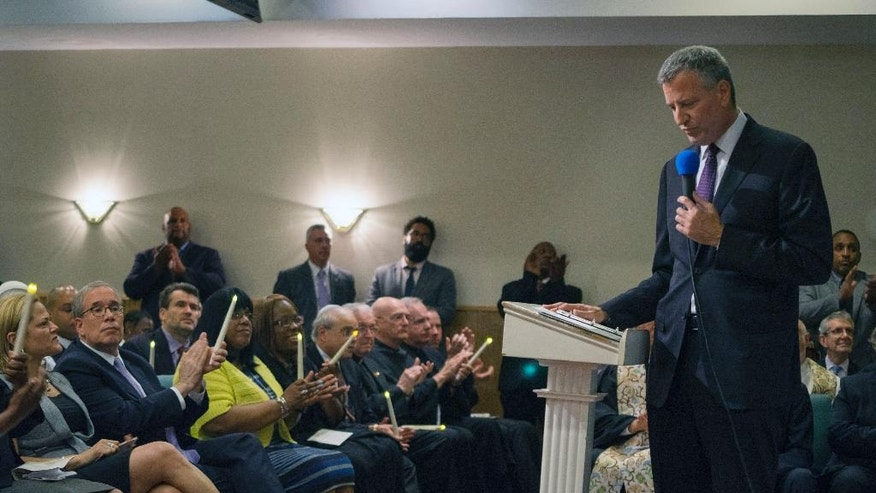 New York City Mayor Bill de Blasio pauses as he speaks during a memorial service for Eric Garner at the Mount Sinai United Christian Church in the Staten Island borough of New York Tuesday, July 14, 2015, just short of a year after Garner died while being taken into custody by New York City police officers. A $5.9 million settlement in Garner's death, a black man who died after being placed in a white police officer's chokehold, was reached with the city this week, days before the anniversary of his death. (AP Photo/Craig Ruttle)