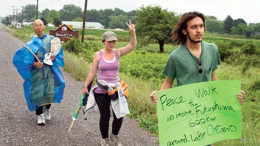 In this July 26, 2012 photo provided by the Northumberland News, Alexander Ciccolo, right, participates in a peace walk through Brighton, Ontario. Law enforcement officials say Ciccolo was arrested after his father, a Boston police captain, alerted authorities that his son was talking about joining the Islamic State group and setting off bombs. (Dave Fraser/Northumberland News via AP) MANDATORY CREDIT