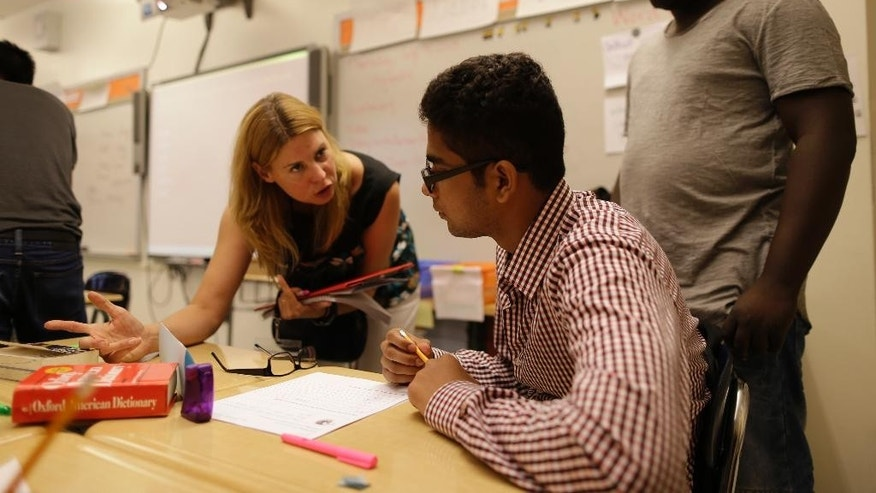 In this Thursday, July 9, 2015 photo, lead teacher Stacey Ward, left, works with Enoush Younus, center, during a High School 1 class at the Refugee Youth Summer Academy, in New York.  (AP Photo/Mary Altaffer)