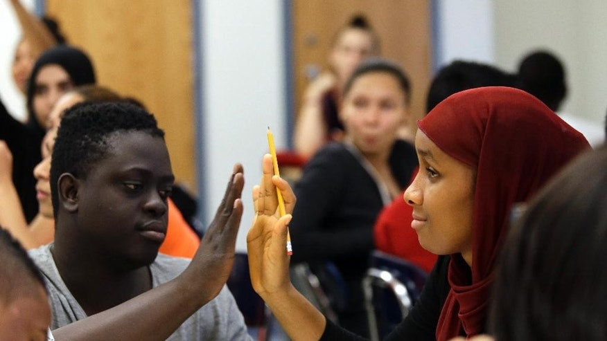 In this Thursday, July 9, 2015 photo, assistant teacher Bassirou Kaba, left, works with one of the students during a High School 1 class at the Refugee Youth Summer Academy, in New York.  (AP Photo/Mary Altaffer)