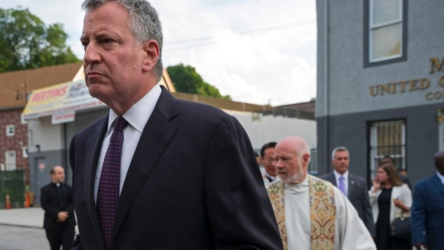 New York City Mayor Bill de Blasio walks to a memorial service for Eric Garner at the Mount Sinai United Christian Church in the Staten Island borough of New York Tuesday, July 14, 2015, just short of a year after Garner died while being taken into custody by New York City police officers. A $5.9 million settlement in Garner's death, a black man who died after being placed in a white police officer's chokehold, was reached with the city this week, days before the anniversary of his death. (AP Photo/Craig Ruttle)