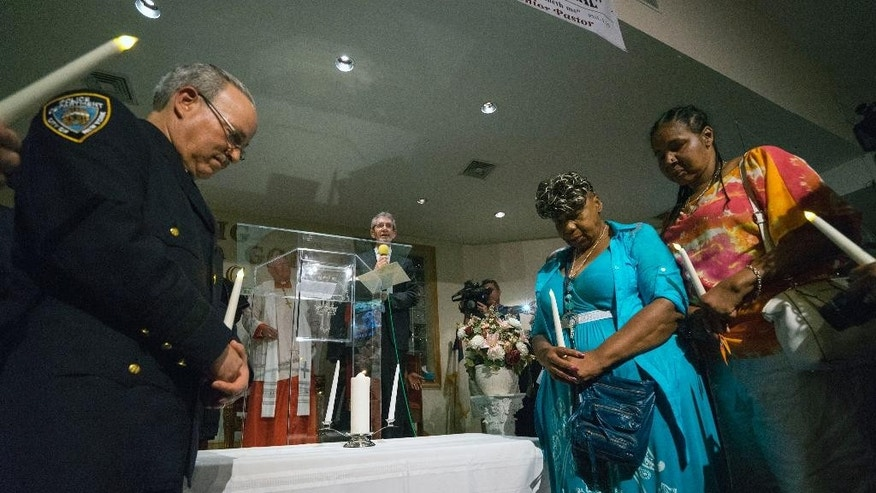 NYPD Staten Island Borough Commander Edward Delatorre, left, stands during a vigil with Esaw Snipes, right, wife of Eric Garner, and  second from right, Gwen Carr, mother of Garner, during a memorial service for Eric Garner at the Mount Sinai United Christian Church in the Staten Island borough of New York Tuesday, July 14, 2015, just short of a year after Garner died while being taken into custody by New York City police officers. A $5.9 million settlement in  Garner's death, a black man who died after being placed in a white police officer's chokehold, was reached with the city this week, days before the anniversary of his death. (AP Photo/Craig Ruttle)