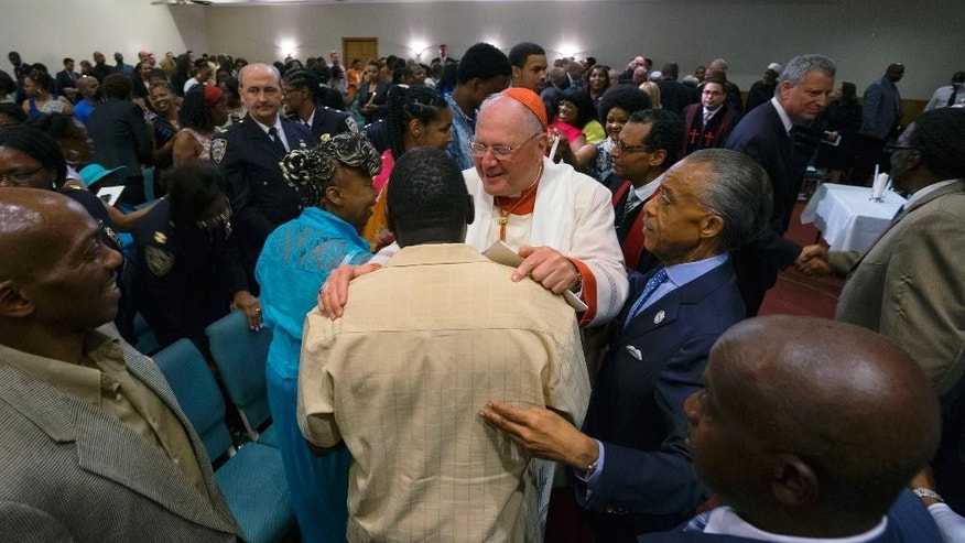 Benjamin Carr, stepfather of Eric Garner, is embraced by Cardinal Timothy Dolan during a memorial service for Eric Garner at the Mount Sinai United Christian Church in the Staten Island borough of New York Tuesday, July 14, 2015, just short of a year after Garner died while being taken into custody by New York City police officers. A $5.9 million settlement in  Garner's death, a black man who died after being placed in a white police officer's chokehold, was reached with the city this week, days before the anniversary of his death. Right is Rev. Al Sharpton and in background upper right is New York City mayor Bill de Blasio. (AP Photo/Craig Ruttle)