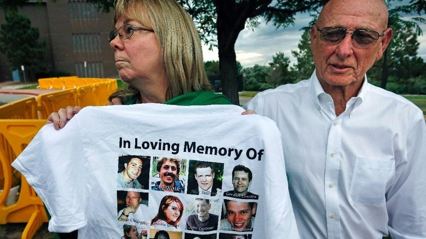 Lonnie and Sandy Phillips, whose daughter Jessica Ghawi was killed in the 2012 Aurora movie theatre massacre, talk with members of the media and display a T-shirt memorializing the twelve people killed in the attack, outside the Arapahoe County District Court following the day of closing arguments in the trial of theater shootings defendant James Holmes, in Centennial, Colo., Tuesday July 14, 2015. (AP Photo/Brennan Linsley)