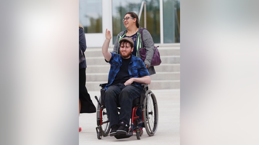 Katie Medley wheels her husband Caleb Medley, who was shot in the face in the 2012 Aurora movie theatre massacre, suffering paralysis and major brain trauma, as the two exit the Arapahoe County District Court following the day of closing arguments in the trial of theater shootings defendant James Holmes, in Centennial, Colo., Tuesday July 14, 2015. Katie Medley was also in the theater during the attack, and was 9-months pregnant at the time. (AP Photo/Brennan Linsley)
