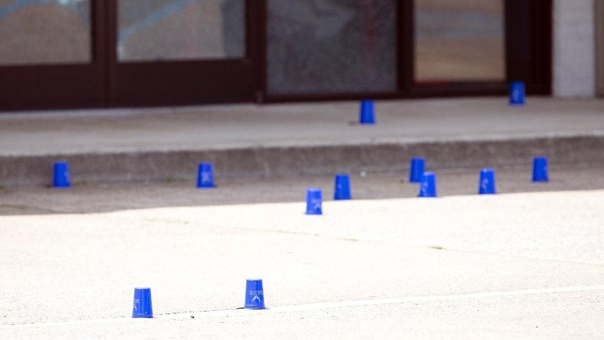 Plastic cups mark evidence outside the Armed Forces Career Center after a gunman open fire on the building Thursday, July 16, 2015, in Chattanooga, Tenn. Authorities say there were multiple casualties including the gunman.   (AP Photo/John Bazemore)