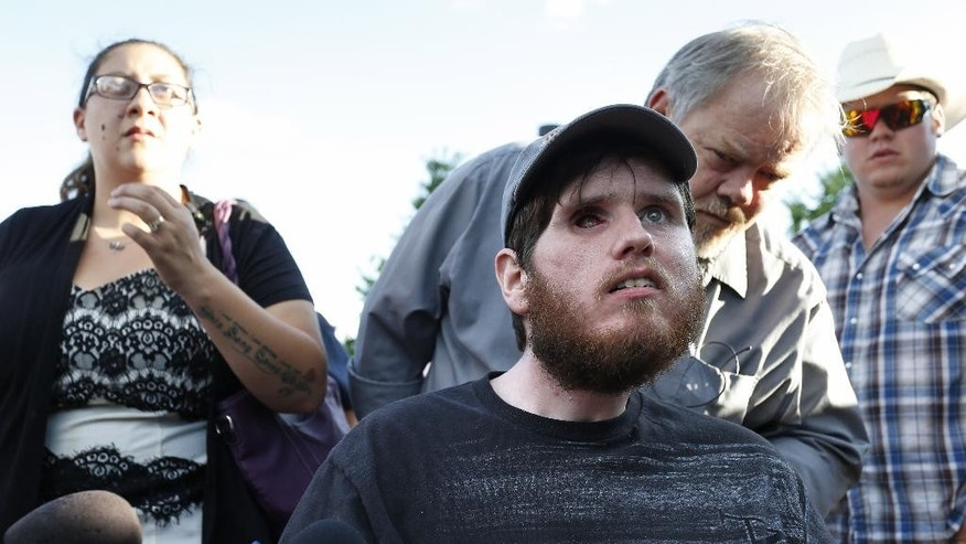 Caleb Medley, who was shot in the face in the 2012 Aurora movie theater massacre, sits in a wheelchair near his wife Katie, left, and other family members as they talk with members of the media after attending the reading of the verdict in the trial of shooter James Holmes at the Arapahoe County District Court in Centennial, Colo., Thursday, July 16, 2015. A Colorado jury on Thursday convicted 27-year-old Holmes of killing 12 moviegoers and wounding dozens of others. (AP Photo/Brennan Linsley)