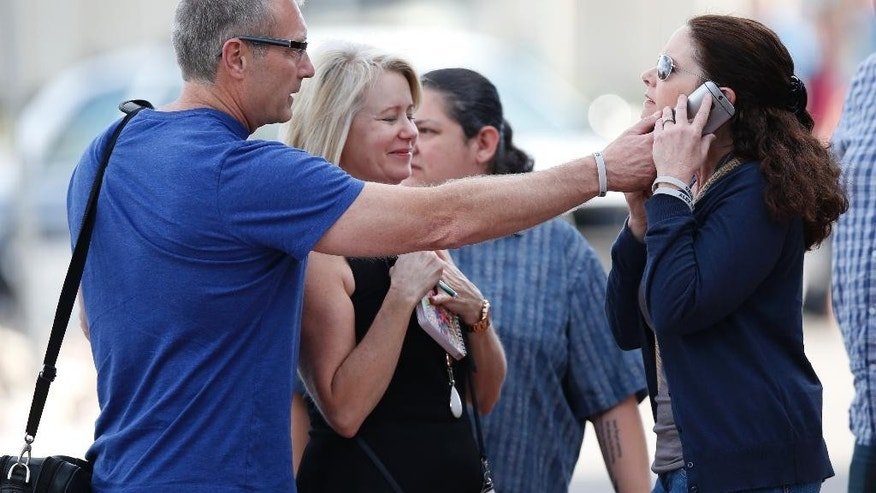 Tom Teves, left, holds a mobile telephone for his wife, Caren, as the couple, who lost their son, Alex, in the 2012 Aurora, Colo., theater massacre, emerge from Arapahoe County courthouse after jurors convicted shooter James Holmes in the killing spree as the trial concluded Thursday, July 16, 2015, in Centennial, Colo. The 27-year-old Holmes, who had been working toward his Ph.D. in neuroscience, could get the death penalty for the massacre that left 12 people dead and dozens of others wounded. (AP Photo/David Zalubowski)