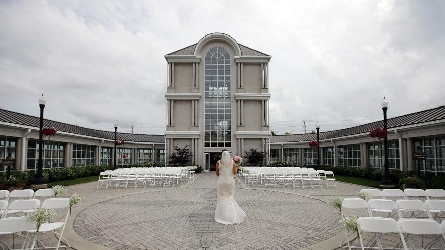 In this June 19, 2015 photo, Danessa Molinder walks towards the Crystal Tower for photos before her wedding  at the Community Life Center, in Indianapolis. The somewhat ironically named Community Life Center sits on cemetery land near a funeral home. (AP Photo/Darron Cummings)