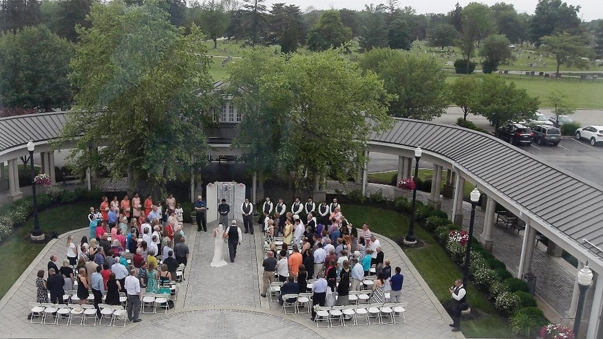 In this June 19, 2015 photo taken through a window, Danessa Molinder and Billy Castrodale are married in the open air courtyard at the Community Life Center, in Indianapolis. The somewhat ironically named Community Life Center sits on cemetery land near a funeral home and also has hosted proms, community banquets and even a breakfast with Santa. (AP Photo/Darron Cummings)