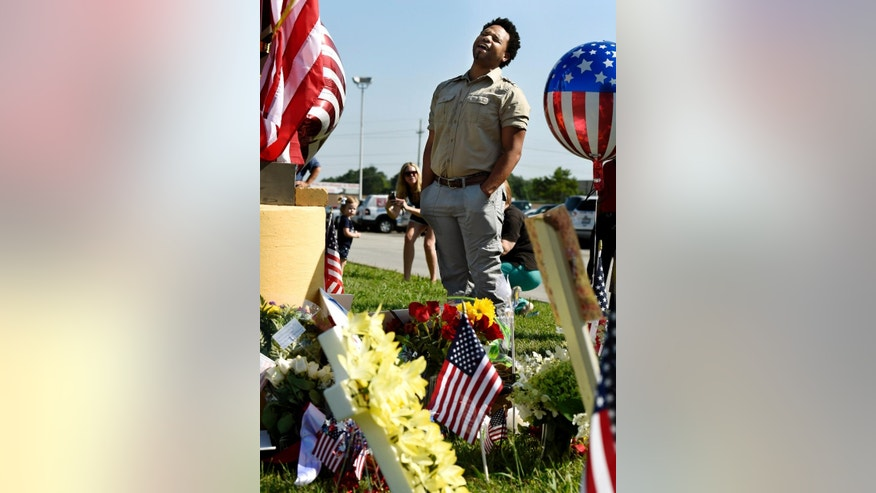 "Michael Dexter sings ""Amazing Grace"" by a makeshift memorial outside the Armed Forces Career Center on Friday, July 17, 2015, in Chattanooga, Tenn. Counterterrorism investigators are trying to figure out why a 24-year-old Kuwait-born man, who by accounts lived a typical life in suburban America, attacked the career center and a Navy-Marine training center a few miles away in a shooting rampage that killed four Marines.  (AP Photo/Mark Zaleski)"