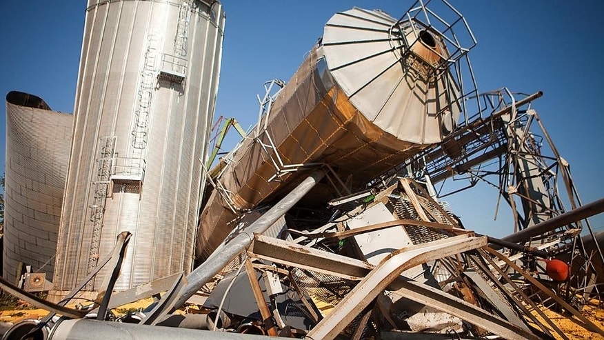 The twisted wreckage of several grain bins lie in a heap Friday July 17, 2015 in Cameron, Ill., the morning after a tornado swept through the city. At least three tornadoes hit communities in the northwest corner of Illinois and the central part of the state late Thursday, causing extensive damage but no significant injuries, officials said. (Steve Davis/The Register-Mail via AP)  MANDATORY CREDIT