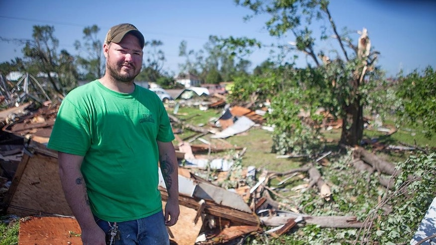 Josh Atwell stands in front of remnants of a trailer he was restoring to move into Friday July 17, 2015 before it was destroyed by a tornado that struck Thursday night in Cameron, Ill., At least three tornadoes hit communities in the northwest corner of Illinois and the central part of the state late Thursday, causing extensive damage but no significant injuries, officials said. (Steve Davis/The Register-Mail via AP)  MANDATORY CREDIT