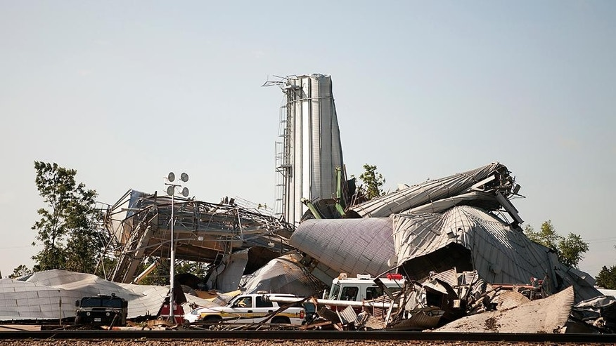 Emergency vehicles surround the twisted wreckage of a grain elevator Friday July 17, 2015 in Cameron, Ill., the morning after a tornado swept through the city. At least three tornadoes hit communities in the northwest corner of Illinois and the central part of the state late Thursday, causing extensive damage but no significant injuries, officials said. (Steve Davis/The Register-Mail via AP)   MANDATORY CREDIT