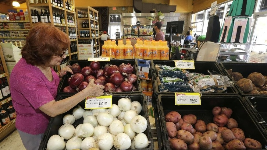 In this photo taken June 12, 2015, shopper Julia Esquivel picks onions at a local grocery store in the Little Havana area of Miami. The Labor Department reports on consumer prices for June on Friday, July 17, 2015. (AP Photo/Alan Diaz)