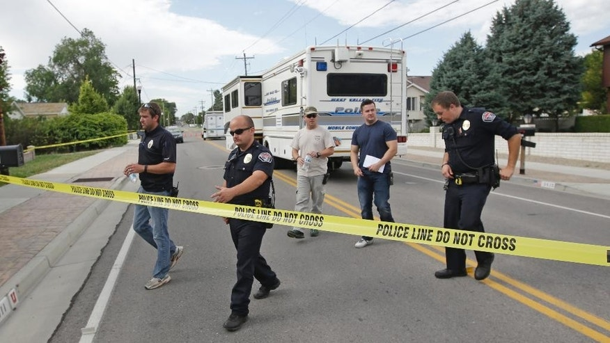 Police officials gather during an investigation after a 12-year-old girl was found dead Friday, July 17, 2015, in West Valley City, Utah. (AP Photo/Rick Bowmer)